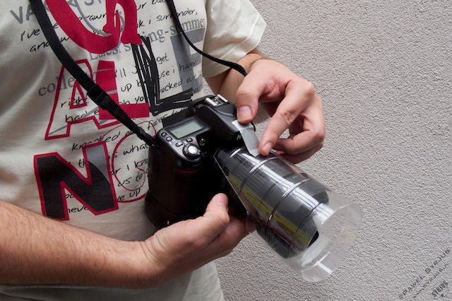 3. Zakładamy butelkę na obiektyw i daszek przyklejamy kawałkiem taśmy klejącej do górnej części aparatu